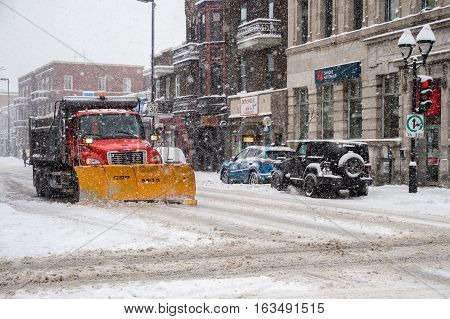 Montreal CA - 29 December 2016: A snowplow in motion on Mont-Royal Avenue during snow storm.