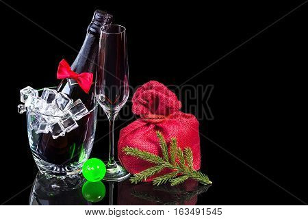 Bottle of champagne in an ice bucket with wineglass and gift in bag