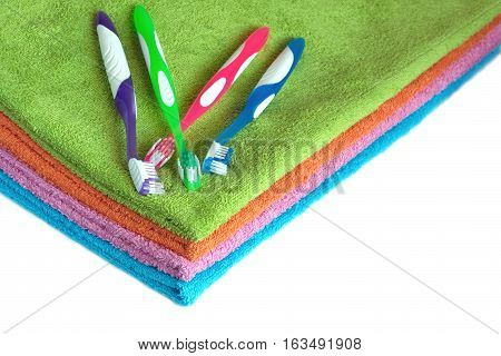 Four clean soft double bath towels set of different colors stacked and four toothbrushes isolated on white background. Side view from corner close-up