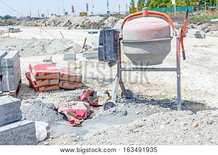 Manually cement mixer machine at building site cement sacks and kerbstone on pallet placed at gravel ground.