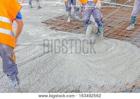 Construction workers are pouring concrete in building foundation directing pump tube on the right direction.