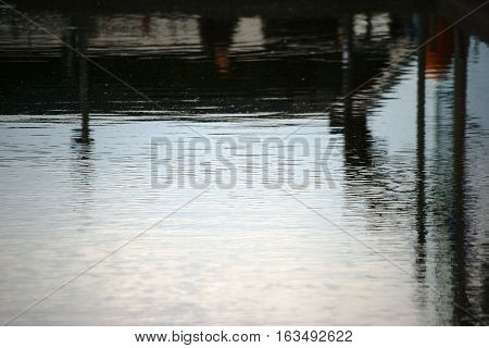The abstract reflections of buildings and piers in the harbor area.