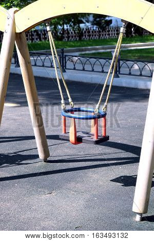 Children wooden swing on ropes, for babies in city park on a summer day close-up