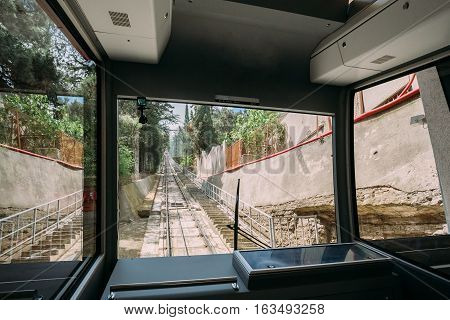 Tbilisi, Georgia. The View From The Contemporary Cabin Of The Funicular To The Straight Rail Track Going Up High Among Green Park In Summer Sunny Day.