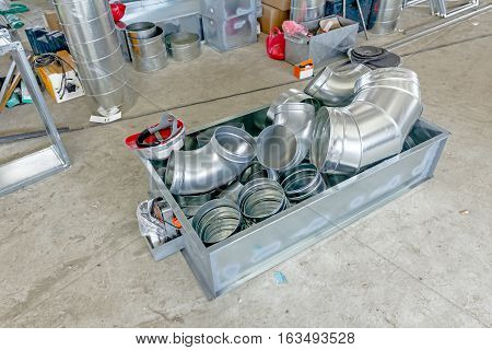 Metal box with pile of zinced ventilation pipes for air conditioning system is placed in metal pallet.