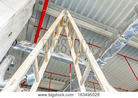 Wooden stepladder and fire fighting system is placed on the ceiling.