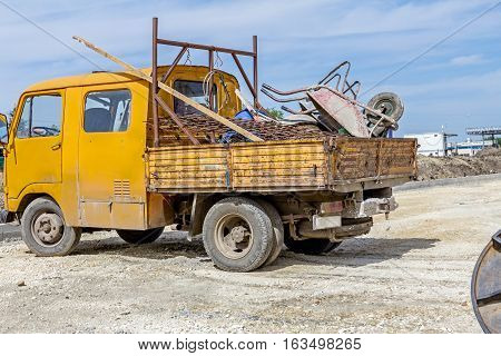 Small yellow truck is parked loaded with various tools at building site