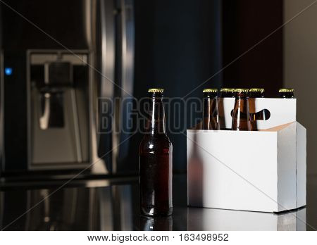 Six pack of brown beer bottles in plain white cardboard carrier with copy space on stainless steel kitchen or bar counter