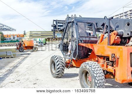 Logistics concept view on telescopic forklift that is carries composite panel walls at construction site.