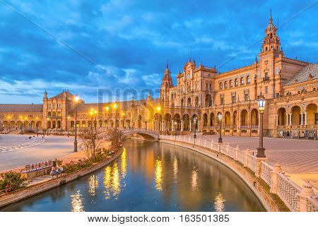 Canal and bridge reflecing in water on Plaza de Espana in the evening Seville Andalusia Spain