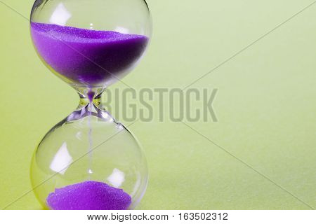 Purple sand clock on yellow background passing time concept.