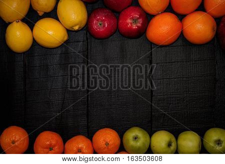 Ripe fruits are laid out on the perimeter on a black wooden background top view an empty space in the middle