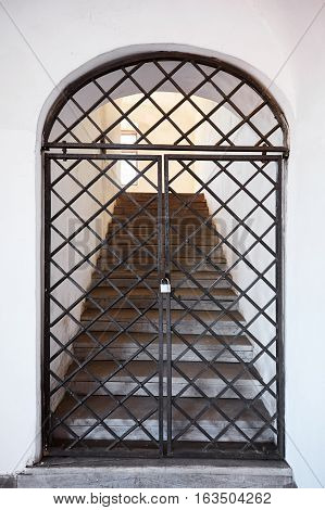 Old metal door in with stairs. Grating.