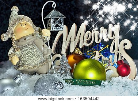 Christmas figurine in snow with Christmas decorations and lettering Merry Christmas