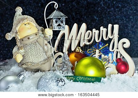 Christmas figurine in snow with Christmas decorations and lettering Merry Christmas.