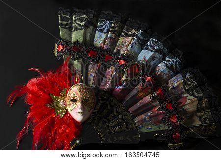 Mask with folding fan. Carnival mask with folding fan on black background photo.