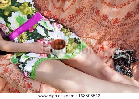 Woman in bright dress lying with a cup of tea