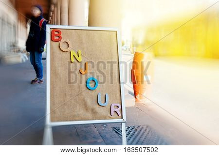 Advertising board with Bonjour word in French city with woman tourist and light flare