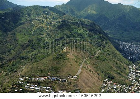 Aerial of Tantalus Mountain with Round Top drive winding up hill past nice houses overlooking Moana on Oahu Hawaii. poster
