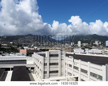 Aerial of Dole Cannery power station and Nuuanu Valley leading to the Mountains on Oahu Hawaii. July 2016. Landscape features Tall buildings Homes and Kamehameha Schools.