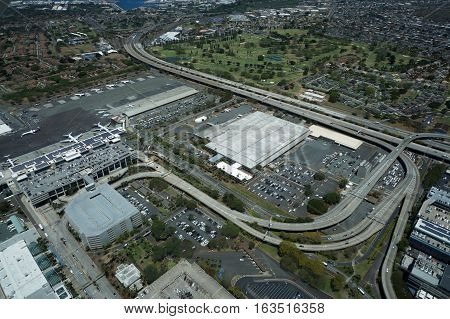 HONOLULU - APRIL 20: Aerial view of planes helicopters Golf Course Parking lots Roads leading into Airport and cars parked by buildings at the Honolulu International Airport HNL next to the water on Oahu Hawaii. April 20 2016.