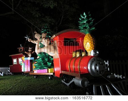 HONOLULU - DECEMBER 14: Hawaiian Figures Drive Shaka and Ride Christmas Train full of Presents Norfolk pine Christmas Tree and a Pineapple for a smokestack in front of Honolulu Hale the Mayor Office as part of Honolulu City Lights runs annually throughout