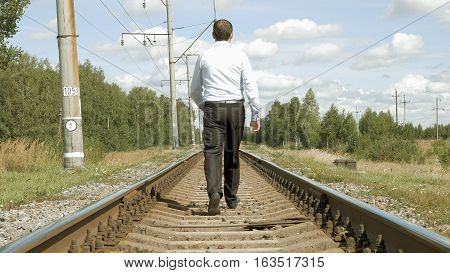 Man in a business dress suit walks along the rails on the railroad path and moves away from camera. Business and society progress and pressure speed and stress concept.