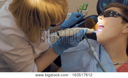 Woman at the dentist clinic office gets dental medical examination and treatment. Close up shot. Odontic and mouth health is important part of modern human life that dentistry help with.