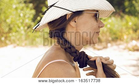 Woman is stroking her long hair and plait outdoors on sunny day. The female is wearing jute straw hat and sunglasses to protect her from sun on the beach. Summer recreation and relax concept.