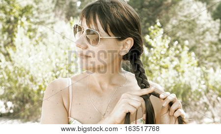 Woman plaits her long hair and stroking it outdoors on sunny day. The female is wearing and sunglasses to protect her from sun on the beach. Summer recreation and relaxation concept.
