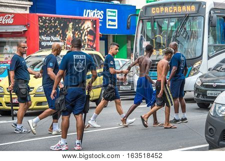 RIO DE JANEIRO, BRAZIL - DECEMBER 30, 2016: Policemen making arrest of criminals and leading them to police cars at Avenida Princesa Isabel during preparation Copacabana to New Year 2017 celebration