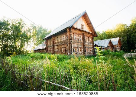 Wooden house classic Slavic style of a log house among the green grass near the forest