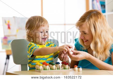 Mother and child learn color size count while playing together. Early education concept.