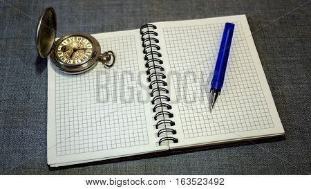 notebook. pocket watch and pen on a gray background
