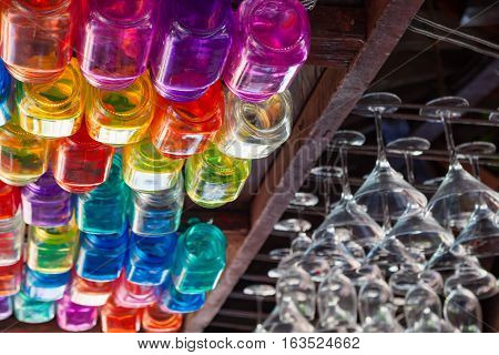 Restaurant interior background with narrow focus. Empty transparent wineglasses rows of colorful beverage glasses hanging on top rack above bar counter. Vintage style wood ceiling.