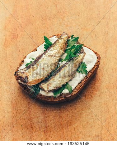 sandwich of canned sprats on rye bread with mayonnaise and parsley and dill on a wooden cutting board close up