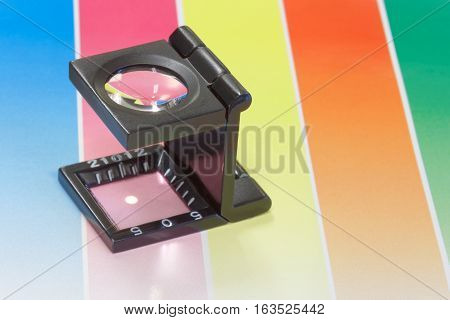 Magnifier or printer's loupe sits on a colorful CMYC test sheet in a pre-press workshop
