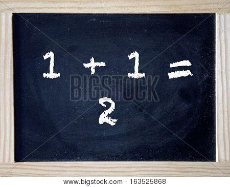 one plus one written on black chalkboard
