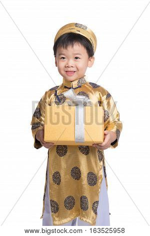 Vietnamese little boy in traditional Aodai, holding a gold gift standing isolated on white background