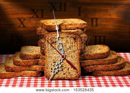 Rusks of wholemeal flour on a table with a clock made with a rusk. Concept of time for a healthy breakfast