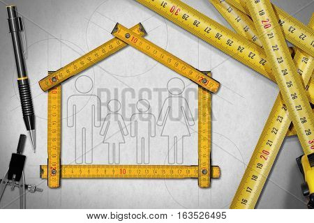 House project concept. Meter ruler in the shape of house with symbol of a family pencil drawing compass and a group of tape measures
