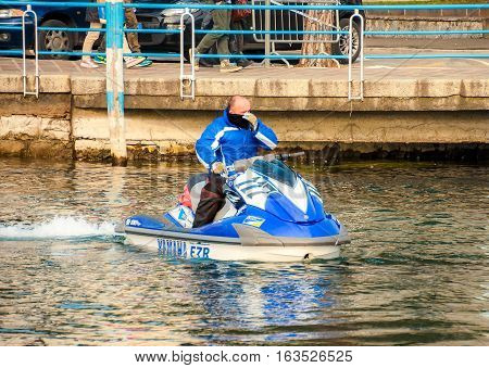 Iseo Italy Feb 16 2013 - man on a blue ski jet watercraft in winter