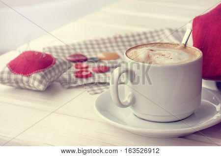 hot frothy cappuccino with cinnamon on a background of domestic sewing lessons / coffee break at home