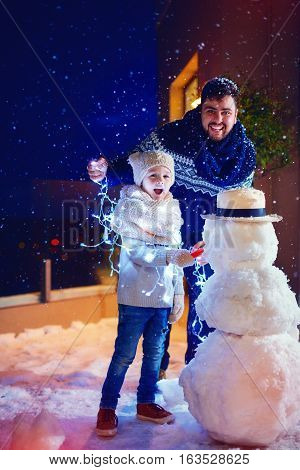 Happy Father And Son Making Snowman In Backyard In The Twilight
