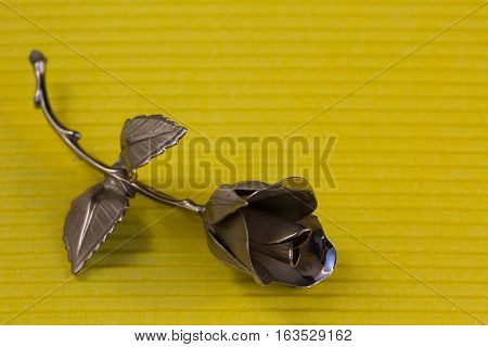 One Metal Rose On A Yellow Background For Holiday Greetings