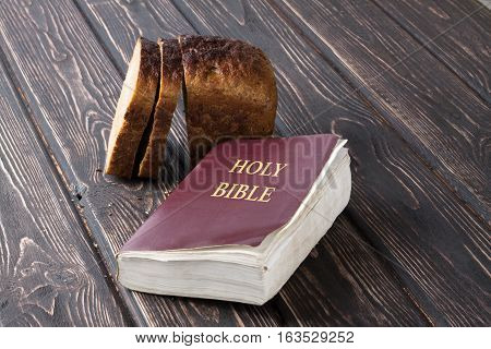 Whole grain bread and Bible close up. Food background