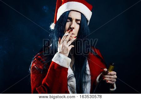 Sexy girl in Santa's costume smoking over dark background