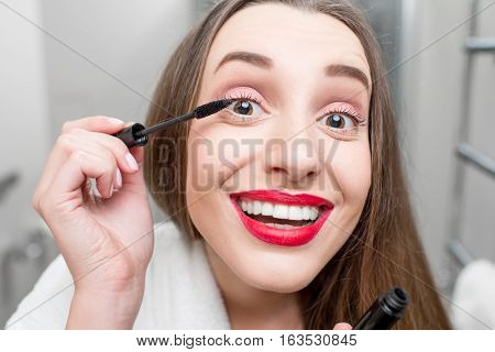 Woman painting eyelashes with mascara in the bathroom