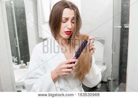 Woman worried about hairloss and splited hair ends standing with comb in the bathroom