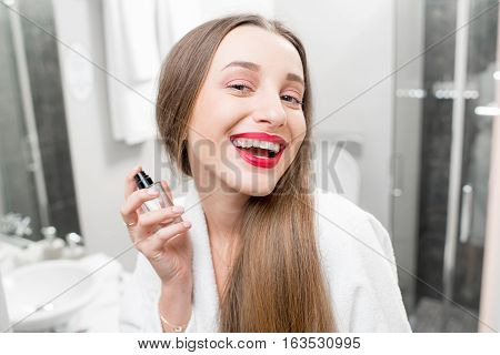 Young smiling woman spraing parfumes in the bathroom